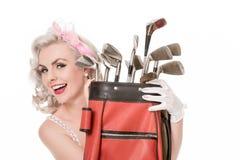 Muchacha retra feliz que mira a escondidas hacia fuera de detrás la bolsa de golf roja, aislada Fotos de archivo libres de regalías