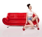 Muchacha retra Pin-para arriba en el sofá de cuero rojo Imágenes de archivo libres de regalías