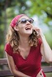Muchacha retra roja que ríe en el teléfono Foto de archivo