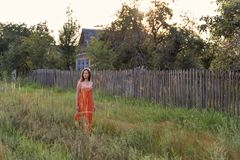 Muchacha retra sola asustada en el campo que camina a lo largo de la alta hierba por la tarde a lo largo de edificios abandonados fotos de archivo