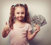 Muchacha rica feliz del niño que sostiene el dinero y que muestra el pulgar encima de la muestra vin Imágenes de archivo libres de regalías