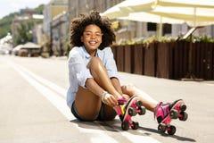 Muchacha rizada alegre que sonríe mientras que pone en pcteres de ruedas Imagen de archivo