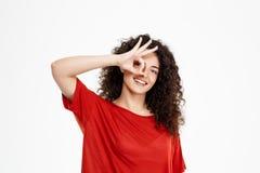 Muchacha rizada blanda que sonríe y que señala la muestra aceptable Imagen de archivo libre de regalías