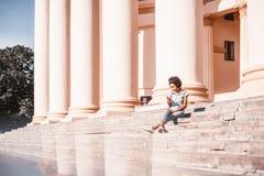 Muchacha rizada brasileña en la escalera con el teléfono móvil, día brillante Fotos de archivo libres de regalías