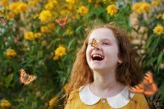Muchacha rizada de risa con una mariposa en su nariz Fotografía de archivo