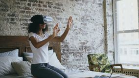 Muchacha rizada del adolescente de la raza mixta que consigue experiencia usando los vidrios de las auriculares de VR 360 de real almacen de video
