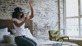 Muchacha rizada del adolescente de la raza mixta que consigue experiencia usando los vidrios de las auriculares de VR 360 de real Foto de archivo