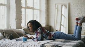 Muchacha rizada del estudiante de la raza mixta lauging usando el ordenador portátil para compartir los medios sociales que mient Fotos de archivo libres de regalías