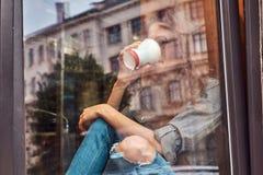 Muchacha rizada del pelirrojo joven que lleva la ropa casual y los vidrios que se sientan en un travesaño de la ventana con un ca Foto de archivo libre de regalías
