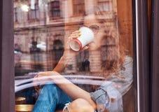 Muchacha rizada del pelirrojo joven que lleva la ropa casual y los vidrios que se sientan en un travesaño de la ventana con un ca Imagen de archivo