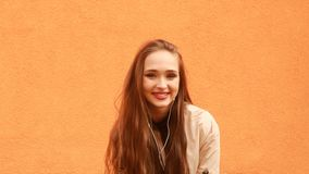 Muchacha rizada divertida del inconformista en auriculares que sonríe, besándose en fondo anaranjado almacen de video