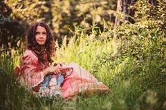 Muchacha rizada feliz del niño en vestido rosado de la princesa en el paseo en el bosque del verano que juega con su muñeca Imagen de archivo libre de regalías