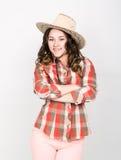 Muchacha rizada hermosa en pantalones rosados, una camisa de tela escocesa y sombrero de vaquero Imagenes de archivo