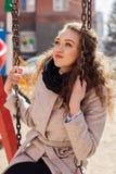 Muchacha rizada hermosa en una capa en la calle Imagen de archivo libre de regalías