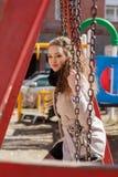 Muchacha rizada hermosa en una capa en la calle Imágenes de archivo libres de regalías