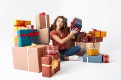 Muchacha rizada hermosa joven que se sienta en piso entre conjeturar de las cajas de regalo cuál está dentro Imagenes de archivo