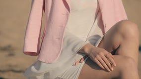 Muchacha rizada joven elegante en el vestido blanco cerca del almacen de metraje de vídeo