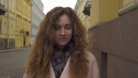 Muchacha rizada joven linda que presenta delante de la cámara almacen de metraje de vídeo