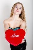 Muchacha rizada joven y hermosa en el corsé azul que sostiene una almohada roja del corazón Imágenes de archivo libres de regalías