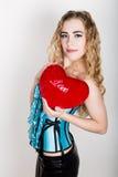 Muchacha rizada joven y hermosa en el corsé azul que sostiene una almohada roja del corazón Foto de archivo