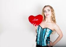 Muchacha rizada joven y hermosa en el corsé azul que sostiene una almohada roja del corazón Foto de archivo libre de regalías