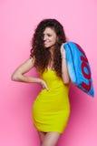 Muchacha rizada joven y hermosa en un vestido amarillo en un fondo rosado que lleva a cabo la almohada azul y risas fotografía de archivo libre de regalías