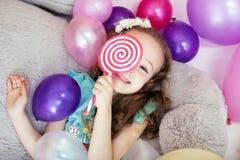 Muchacha rizada juguetona que oculta detrás de la piruleta Fotos de archivo libres de regalías
