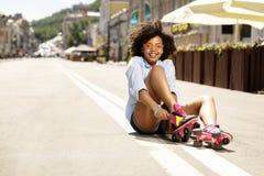 Muchacha rizada linda que pone en pcteres de ruedas en la calle Foto de archivo
