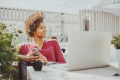Muchacha rizada negra con el ordenador portátil en café Foto de archivo libre de regalías