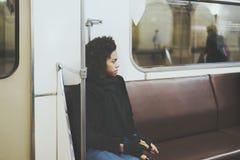 Muchacha rizada negra en el carro del metro, mirando a un lado Foto de archivo libre de regalías