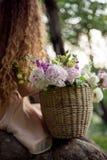 Muchacha rizada que se sienta en un árbol con la cesta de flores Fotografía de archivo libre de regalías