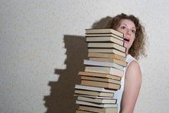 Muchacha rizada que sostiene una pila de libros Imagen de archivo libre de regalías