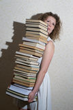 Muchacha rizada que sostiene una pila de libros Fotos de archivo libres de regalías