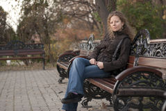 Muchacha rizada rubia que se relaja en un parque Fotografía de archivo
