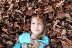 Muchacha rodeada por las hojas fotos de archivo
