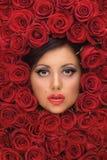 Muchacha rodeada por las rosas rojas Fotografía de archivo