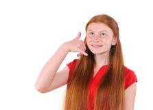 Muchacha roja del adolescente del pelo en una camisa roja que me muestra a una llamada muestra Fotografía de archivo