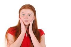 Muchacha roja del adolescente del pelo en una camisa roja que muestra una sorpresa sincera Imagen de archivo libre de regalías