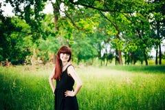 Muchacha roja del pelo de la belleza feliz joven en naturaleza adentro Foto de archivo libre de regalías
