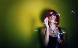 Muchacha roja del pelo que hace burbujas Foto de archivo