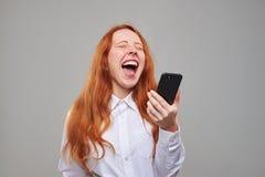 Muchacha roja del pelo que ríe mientras que sostiene un teléfono móvil Fotos de archivo