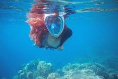 Muchacha roja del pelo subacuática en el mar tropical Tubo respirador en mascarilla completa fotografía de archivo