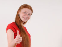 Muchacha roja del tennager del pelo en mostrar rojo de la camisa pulgares-para arriba Fotos de archivo