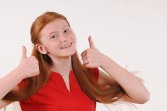 Muchacha roja del tennager del pelo en mostrar rojo de la camisa pulgares-para arriba en ambas manos Imagen de archivo libre de regalías