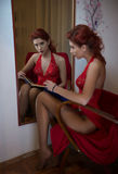 Muchacha roja hermosa del pelo con el vestido rojo largo del cordón que sostiene un libro delante de un espejo grande de la pared Fotografía de archivo