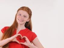 Muchacha roja joven del pelo que muestra forma del corazón con las manos en fondo gris Foto de archivo libre de regalías