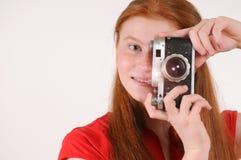 Muchacha roja joven del pelo que sostiene la cámara del vintage contra fondo gris Imagen de archivo libre de regalías