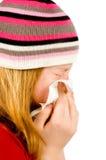 Muchacha roja joven que sopla su nariz Foto de archivo libre de regalías