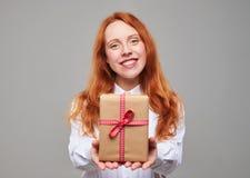 Muchacha roja preciosa del pelo que da la caja de regalo Fotos de archivo