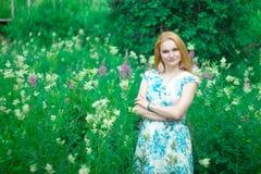 Muchacha roja que se coloca en un prado de la flor foto de archivo